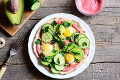 Home tortilla piled high with fried quail eggs, avocado, cucumber, sesame seeds and parsley and lathered with beetroot hummus Royalty Free Stock Images
