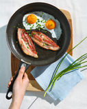 Home traditional breakfast with eggs. And bacon on the pan royalty free stock photography