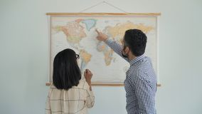 Home travel planning on world map. Couple discuss their adventure travel around the world. Man points with his finger on directions on big world map hanged on stock footage