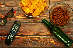 Home TV party concept. Home 3D TV party concept with bottle of lager beer and salted snacks on wooden surface Stock Photos