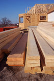 Home under construction. Lumber with a home under construction in the background stock photography