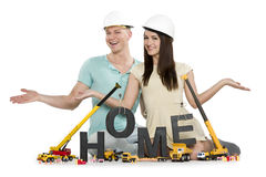 Home under construction: Happy couple with machines building hom Stock Images