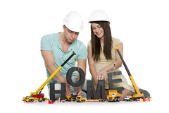 Home under construction: Joyful couple with machines building ho Royalty Free Stock Image