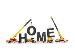 Home under construction: Machines creating home-word. Stock Photos