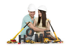 Home under construction: Overjoyed couple with machines building Royalty Free Stock Photography