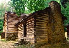 HOME velha do pioneiro do registro com uma chaminé da rocha. Foto de Stock