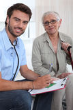 Home visit. Male nurse visiting an elderly patient Royalty Free Stock Photos