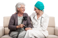 Home visit nurse and old woman with crutch Royalty Free Stock Images