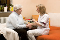 Home visit nurse with senior. Nurse makes home visit and gives senior the hand Royalty Free Stock Photography