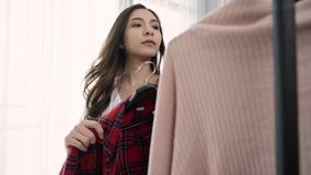 Home wardrobe or clothing shop changing room. Asian young woman choosing her fashion outfit clothes in closet at home or store. Girl think what to wear sweater stock footage