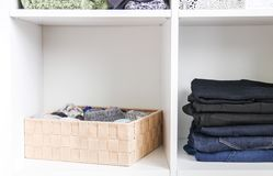 Home wardrobe with different clothes. Small space organization. The contrast of order and disorder. Vertical storage royalty free stock photos