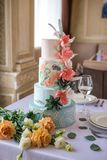 Home wedding for-tiered cake on the table in the restaurant decorated with pink roses and green leaves in a rustic style. A beautiful home wedding for-tiered stock photo