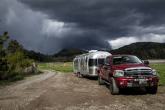 Home is Where the Road Ends. Red Dodge 2500 Ram pulling a 1990 Airstream Excella at road's end with storm clouds in the background Royalty Free Stock Image