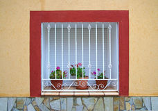Home window with bars and flowers royalty free stock images