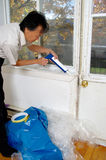 Home  window and door winter preparation. Homeowner old home window and door winter preparation. silicone caulking airtight sealant application for energy Royalty Free Stock Image