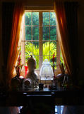 Home Window. Glass table full of decors beside the window stock photo