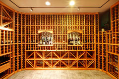 Home wine cellar design idea. Bright home wine cellar with wooden storage units and arch with bottles royalty free stock photos