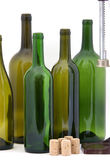 Home wine making items. Several empty wine bottles and new corks against a white background Royalty Free Stock Photography
