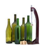 Home winery items. Five wine bottles with wine corker and several corks for use in home wine making Stock Image