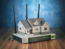 Home wireless network. House and wi-fi router on wooden table an Stock Photo