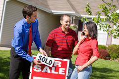 Home: Woman Calls Family With Good News of Home Purchase. Extensive series of a Caucasian Real Estate Agent and African-American Couple in front of a home Royalty Free Stock Images