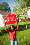 Home: Woman Holds Up For Sale Sign. Extensive series of a Caucasian Real Estate Agent and African-American Couple in front of a home Stock Image