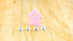 HOME word of cube letters in front of lilac coloured house symbol on wooden surface Royalty Free Stock Images