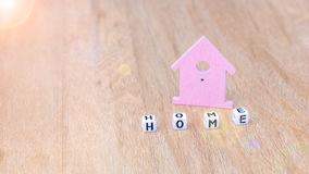 HOME word of cube letters in front of lilac coloured house symbol on wooden surface Stock Photos