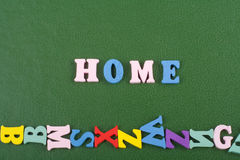 HOME word on green background composed from colorful abc alphabet block wooden letters, copy space for ad text. Learning Stock Photo