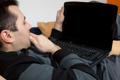 Home Work. Young man working on his laptop from bed Royalty Free Stock Image