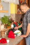 Home work in the kitchen. Man washing dirty dishes in the kitchen sink. Domestic cleaning up after the party. Stock Image