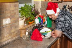 Home work in the kitchen. Man washing dirty dishes in the kitchen sink. Domestic cleaning up after the party. Stock Photo