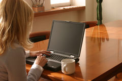 Home worker. Woman typing on a keyboard at home Royalty Free Stock Images