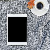 Home workplace with coffee cup on knitted plaid. Creative square autumn flat lay overhead top view stylish home workspace with tablet notebook coffee cup cozy royalty free stock image