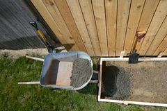 Home yard concrete slab project with wet cement. A backyard, DIY home concreting project with wet cement, wheelbarrow, shovel, wooden fence and form work Royalty Free Stock Photography