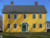 Home: yellow house green door. New England yellow house with green door and Christmas wreath Royalty Free Stock Image
