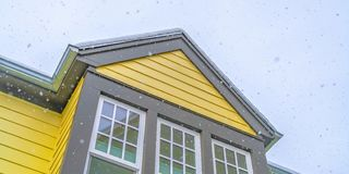 Home with yellow wall and glass windows against cloudy sky in Daybreak Utah. The roof is covered with a sheet of fresh snow during winter season stock photo