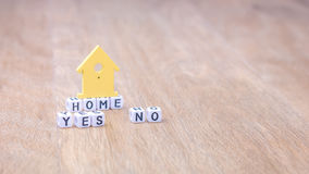 HOME YES NO horizontal word of cube letters with green house symbol on wooden surface Stock Photography