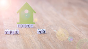 HOME YES NO horizontal word of cube letters with green house symbol on wooden surface Stock Image