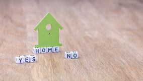 HOME YES NO horizontal word of cube letters with green house symbol on wooden surface Royalty Free Stock Photo