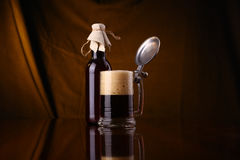 Homebrew beer. Bottle of homebrew beer with a full glass of beer over a draped background Royalty Free Stock Images