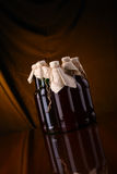 Homebrew beer. Bottles of homebrew beer over a draped background Royalty Free Stock Photos
