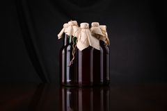 Homebrew beer. Bottles of homebrew beer over a draped background Stock Image