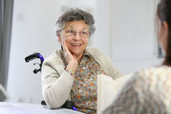 Homecare for the elderly woman. Homecarer reading book to old women in nursing home Royalty Free Stock Photos