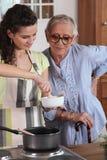 Homecare que cocina para la mujer mayor Fotos de archivo