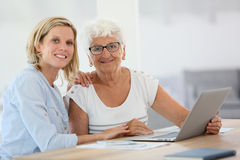 Homecarer with elderly woman using laptop Royalty Free Stock Image