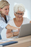 Homecarer and elderly woman using laptop Stock Photos