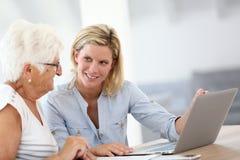 Homecarer en bejaarde dame die laptop met behulp van Stock Afbeeldingen