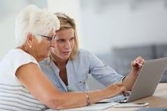 Homecarer und ältere Personen, die Laptop verwenden stockfoto