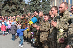 Homecoming. LUTSK, UKRAINE - MARCH 27, 2015: Children welcome soldiers who returned home from the zone of military operations in eastern Ukraine Royalty Free Stock Photos